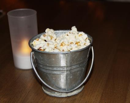 at dinner a small pail of popcorn on your table continues the tavern theme but low lighting from bulbs strung across the ceiling creates an ambiance that