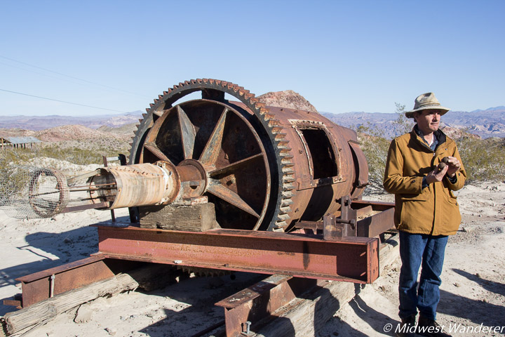 Tour guide, Gabe, standing with rusted ining equipment